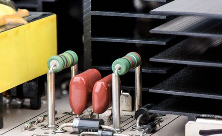 Resistors with capacitors and cooling radiator grill in the background close-up. The world of electronics.
