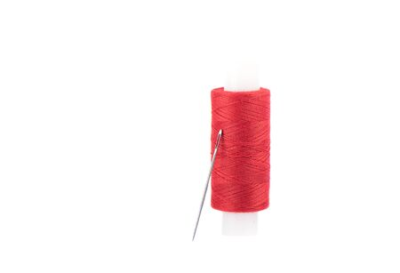Close-up photo of a spool with red thread and a needle isolated over white background.
