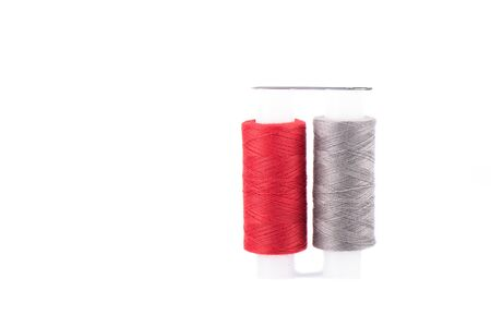 Close-up photo of a spool with red and gray thread and a needle isolated over white background.