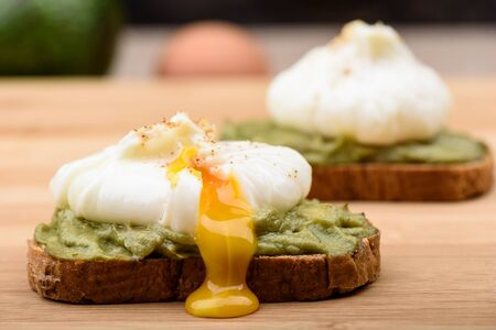 Leaking poached yolk. Sandwiches with poached egg and avocado paste on cereal bread. Healthy lifestyle.
