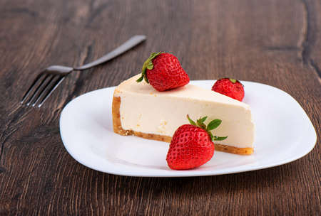 Slice of cheesecake with strawberries on a white plate over wooden background.