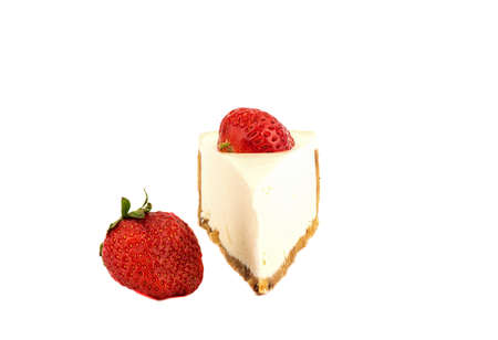 A strawberry next to a slice of cheesecake and half a berry on top.