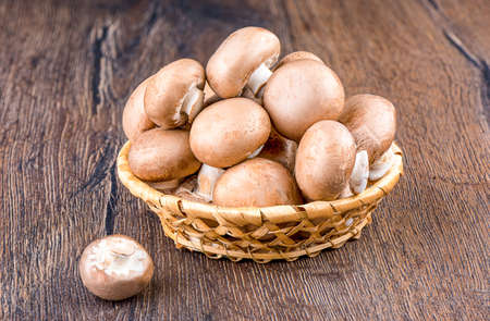 Champignon mushrooms in a wicker basket and one on the table. Close up. Stock Photo
