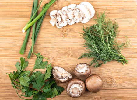 Top view. Chopped and whole mushrooms, green onions, parsley and dill on a wooden background with space for text. Copy space. Stock Photo