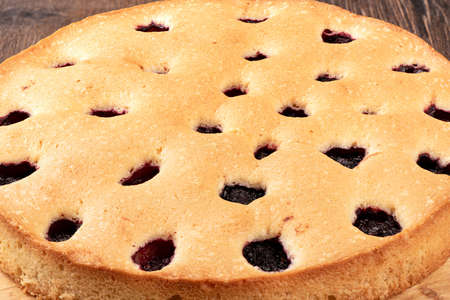 Close-up of a pie with blackberries on a cutting board over a wooden background. Food background.