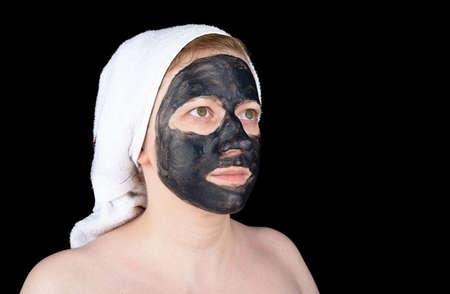 Beautiful young woman with black cosmetic facial scrub mask. Facial skin care.