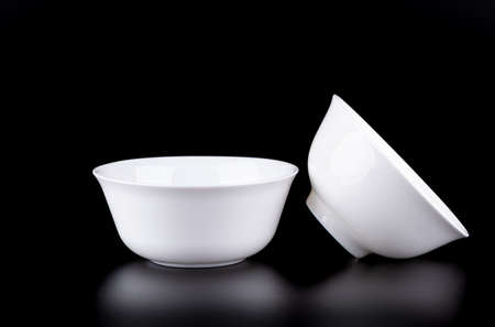 Two white porcelain bowls on a black background.