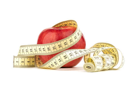 Red apple with measuring tape isolated on white background. Imagens