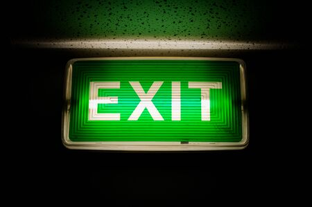 Glowing green exit sign on dark background Stock Photo - 8236232