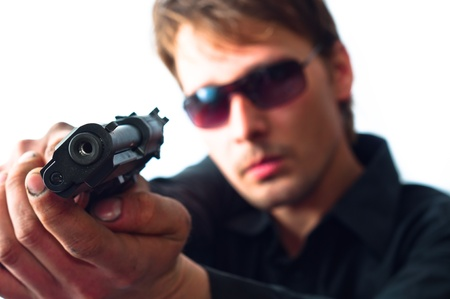 glock: Man holding gun in dirty hands with focus on pistol  weraing sunglasses Stock Photo