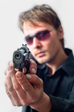 de maras: Hombre con enfoque de pistola en pistola con manos sucias