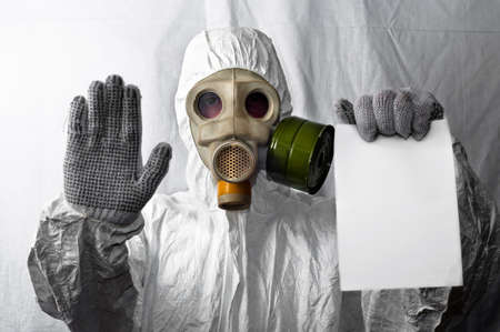 Man in gasmask showing white paper