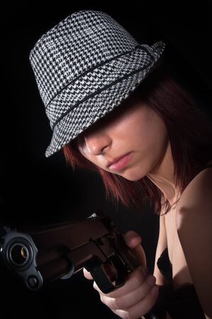 Girl with hat pointing gun photo