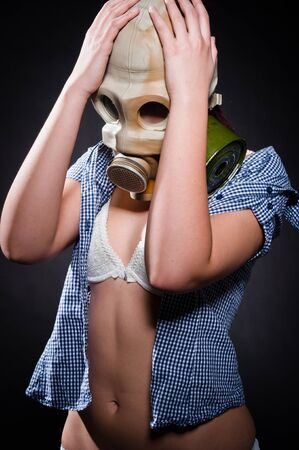 Girl in gasmask holding her head photo