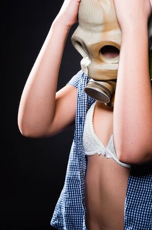 Girl wearing gasmask and white lingerie holding her head photo