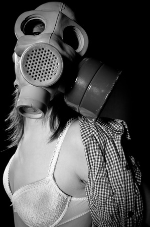 Girl in gasmask and lingerie against black background in black and white photo