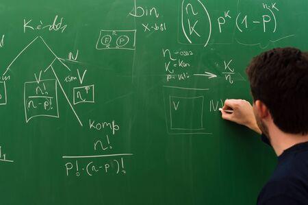 Młody student pisania formuł na zielonej tablicy kredowej Zdjęcie Seryjne