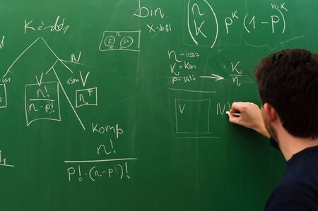 Young student writing formulas on green chalk board Stock Photo - 9485646