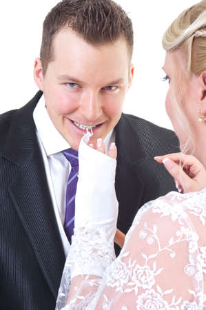 Groom undressing bride while taking off her gloves photo