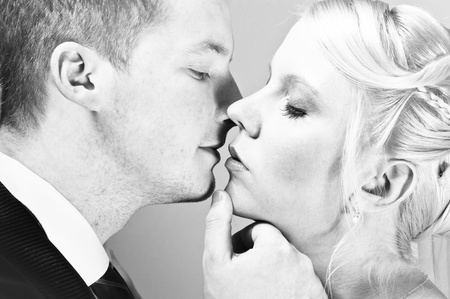 Beautiful young couple kissing in black and white photo