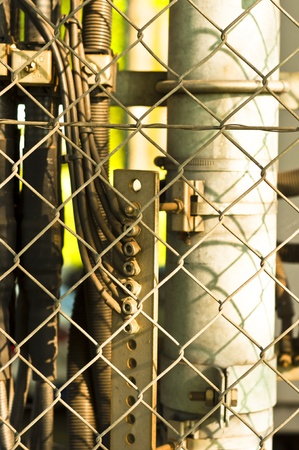 power lines and pipes with steel fence photo
