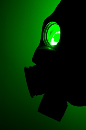 Silhouette of a gas mask in green light photo