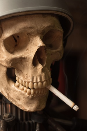 Cigarette burning down in the mouth of the dead photo