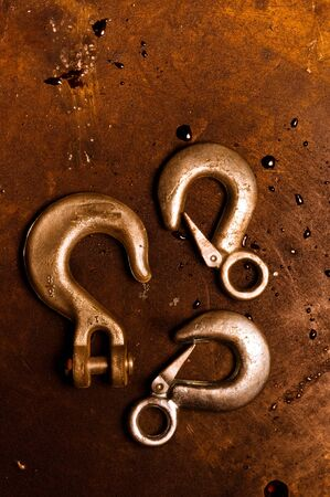 cleek: Rusty crane hooks on metal plate