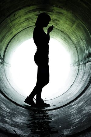 sewer pipe: Silhouette of a young girl smoking in sewer pipe