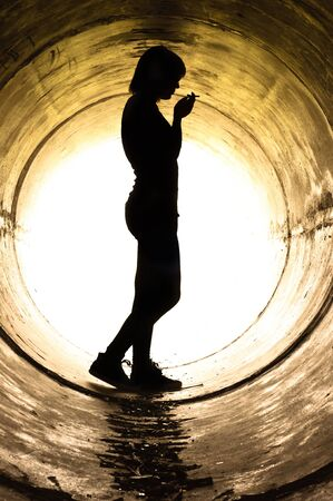 Silhouette of a young girl smoking in sewer pipe photo