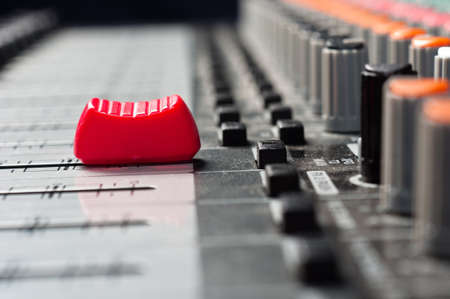 Part of an audio sound mixer with buttons and a slider photo