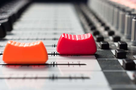 adjuster: Orange and  red slider on a sound mixer with blurry background