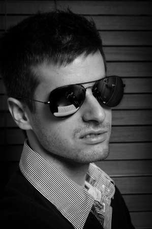 Close-up of a young man in sunglasses against blinds in black and white Stock Photo - 9511405