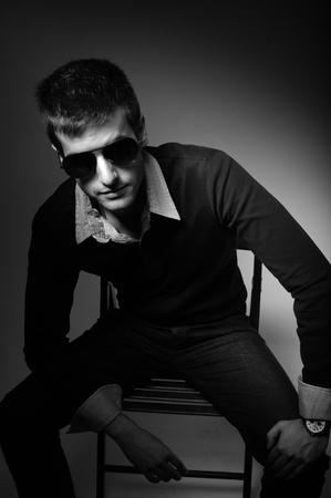 Young man sitting in chair  in sunglasses in shirt in black and white Stock Photo - 9510891