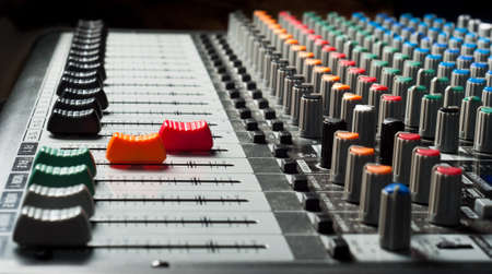 Part of an audio sound mixer with buttons and sliders photo