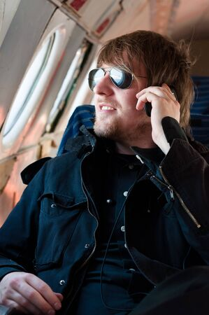Handsome young man traveling on old airplane with phone at his ears Stock Photo - 9511321