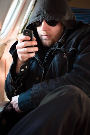 Hooded man looking at his cellular phone in an old airplane Stock Photo - 9511043