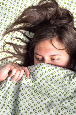 scared girl: Young scared girl hiding under blanket Stock Photo