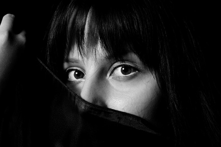 Young arabic girl hiding her face with a scarf in black and white photo