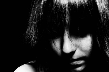 A sad girl looking down with her eyes unseen in black and white Stock Photo - 9594929