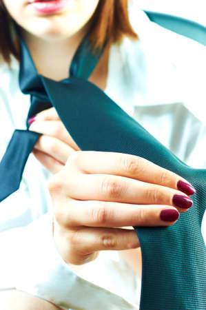 Business woman dressing for work, putting tie on photo