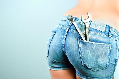 culo: Parte inferior de una mujer con pantalones cortos y llaves y herramientas en su bolsillo