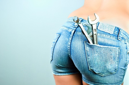 frauenarsch: Unteren Teil einer Frau mit kurzen Hosen und Schraubenschl�ssel und Tools in ihre Tasche Lizenzfreie Bilder