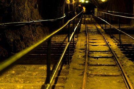 Railway in abandoned mine with yellow lights Stock Photo