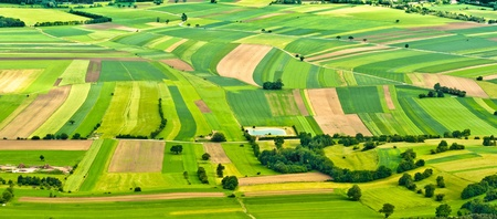 cultivated land: aerial view of green fields and slopes Stock Photo