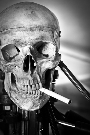 Closeup of a human skull on robot body with cigarette in mouth photo