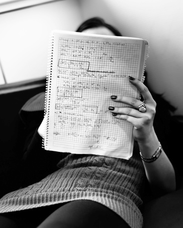 young girl reading notes on a couch photo