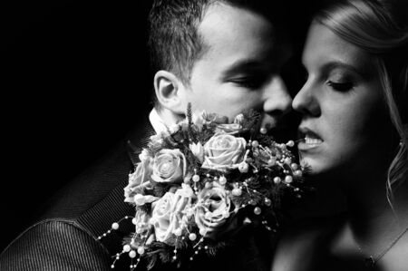 young couple in wedding wear with bouquet of roses photo