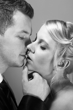 young couple in wedding wear kissing photo