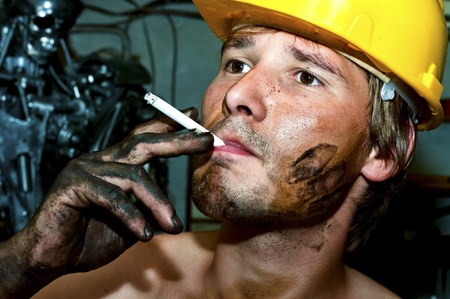 Worker covered in oil smoking Stock Photo - 10193672
